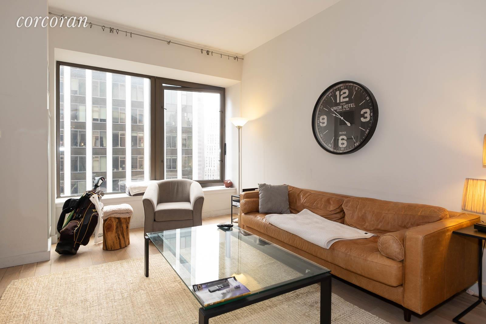 """This lavish apartment at 75 Wall Street, New York, NY 10005 is currently available for short-term or full year rental.  It can be furnished or rented unfurnished as you please. In-person, virtual and video tours are available. This vast Studio with a """"Home-Office"""" has everything one needs from a washer/dryer to a fully equipped kitchen with an island and a modern bathroom with a tub as well as a shower stall.  The main room looks over a small triangular park with lovely South-Western light. The passage from the front door has plenty of closets and one with the Bosch washer and dryer stack.  The Home-Office area which is approximately 81/2' by 81/2'  can easily accommodate at queen-sized bed and some additional furniture,This is a full-service building which was a """"new development"""" about ten years ago, so there are some very high end amenities and finishes.  Currently, the roof deck and lounge are open with social distancing. Residents are entitled free access to the breathtaking roof deck which looks in all directions over the New York Harbor, East River, all the bridges and more,  There is a full gym which is open by appointment, lounges, laundry and more.Lock in the rent on this great apartment for 18 months or just rent for 3! Ask about additional possibilities."""