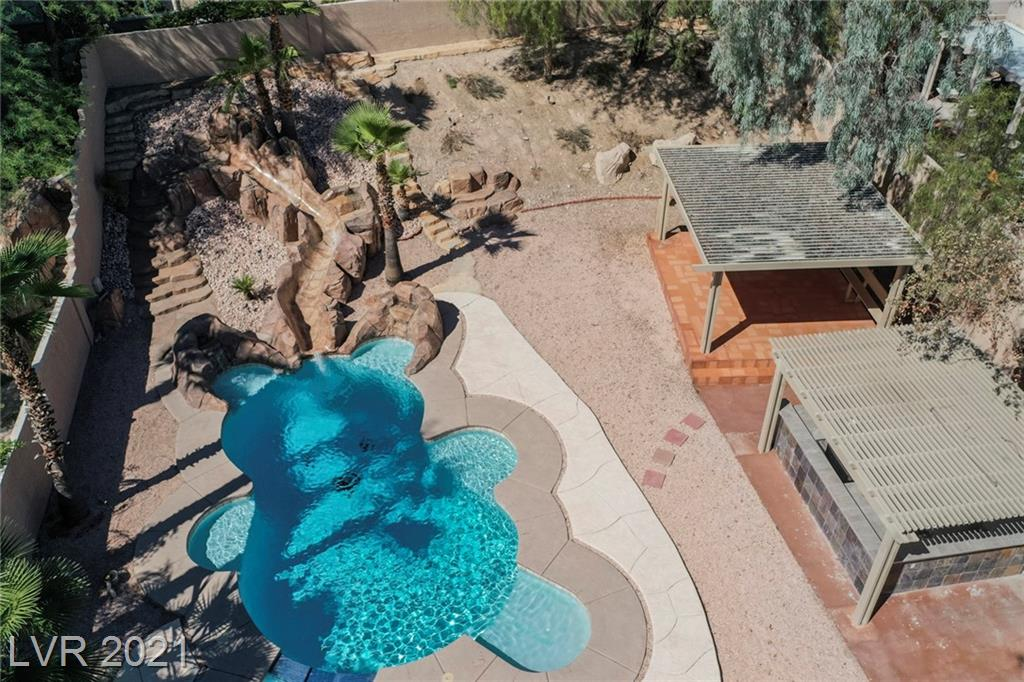 Must see this recently renovated beautiful two-story home in the heart of Summerlin.  Spacious living areas featuring over 2,400 + sq. ft, four bedrooms, three baths, and a three-car garage. The stunning kitchen has opulent finishes, custom cabinets with lighting, stainless steel appliances, and quartz countertops. This home is equipped with smart thermostats,smoke detectors irrigation system,and much more. The open floor plan will lead you upstairs with a loft entering into the primary retreat with a balcony overlooking the backyard, a HUGE walk-in closet, and a brand-new custom shower with two showerheads and rainfall and in-shower lighting.  The spacious backyard is an entertainer's paradise with a covered outdoor kitchen and two covered patio spaces overlooking the expansive area for a fire pit and the very fun bear-shaped saltwater swimming pool with a waterslide. The nighttime outdoor lighting features over 26 hue color-changing lightbulbs that can make any event a fun gathering!