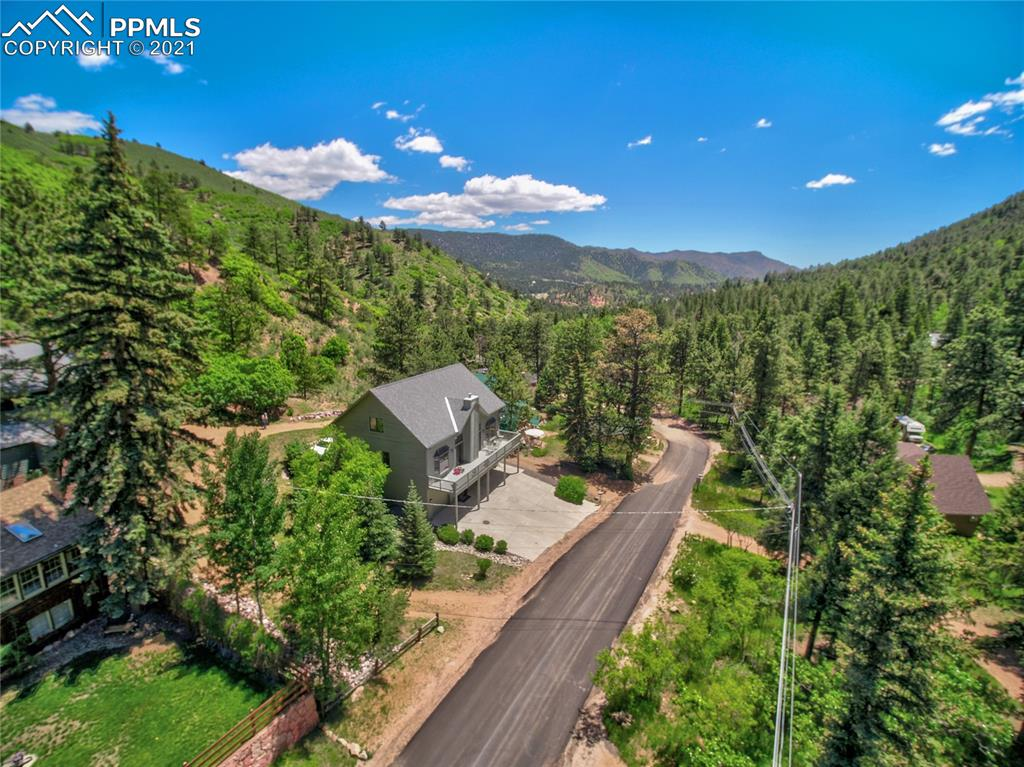 Welcome to this stunning Colorado Mountain home sitting on one of GMF's most desired streets. As you enter in to the Great Room you are greeted by all of the open, light spaces. Warm and inviting with a gas log Fireplace w/access to the 9X45 ft. Deck  where you will litterly have an extention to your Living Room in the Summer, you can enjoy the panoramic mountain views and the wildlife around you and the sound of the mountain stream. The Kitchen w/lots of cabinets & counter space, double ovens, pantry & perfect Breakfast Nook. Back entrance brings you in to smaller room w/desk    & Laundry area in enclosed closet. Seperate Dining room w/so much light. Be sure to take notice of all the beautiful ceilings through out this home. The master is just off the great room w/large walk in closet & 6 foot Kohler Birthday Bathtub. The upper level has a spacious loft & 2 large Beds w/full Bath, behind the closets you will find another door w/more storage. Basemant level boasts 3 totally seperate Garages & full Office, full Bath and Library & large walk in closet here as well.This custom home has so many extra functional touches. You are minutes from to hike the Falls & Catamount , walking distance to our sweet little town of Green Mountain Falls & all it has to offer w/restaurants, fishing, shopping, swimming, biking & hiking. Easy access to Woodland Park or Colorado Springs and many different ski area for Winter fun. If you have ever dreamed of the perfect balance in a comfortable mountain cabin and being a little pampered with the luxury you deserve then welcome home to this perfect spot on Belvidere Avenue, Green Mountain Falls, Colorado.