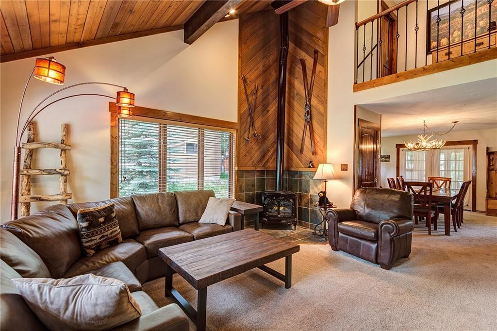 The living room opens to the dining area. Love those vaulted ceilings!