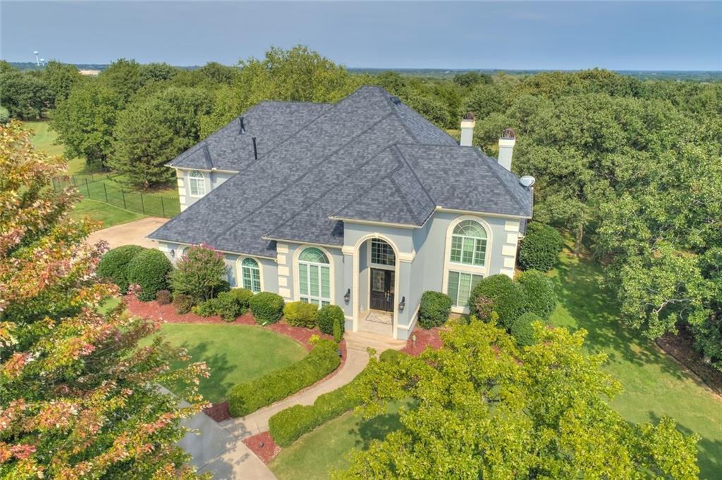 """You'll """"Fall"""" in love with this magnificent acreage with a pool in popular SE Edmond from the minute you walk in! This elegant yet comfortable home boasts:New high impact roof/gutters,wrought iron fence & pool cover new in '19;new Anderson windows all around in '18 &'19;New exterior paint '17;Pella doors'16; Kitchen (new appliances, designer granite)& master bath(including designer granite, FP & heated floors)remodeled in '10;Newer gleaming wood floors through out the entire downstairs;Soaring 20"""" ceilings make for lots of light & open space; 2 living areas, 2 dining, butler's pantry,the master & a MIL bed or 2nd master w/full bath down;a bonus/game room & a hobby/craft room or 5th bed, along w/ 2 large beds w/a Jack & Jill bath up;The sunny kitchen opens to the large living room w/a wall of windows overlooking the wooded acreage & private concrete pool(new pump & heater w/freeze protector '17); additional yard beyond the fenced pool area has 2 well pumps, perfect for gardeners.Hurry!"""