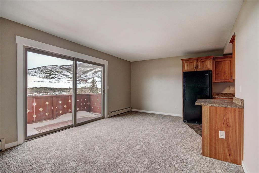 Spacious living room with new sliding glass door, new trim and new carpet throughout.