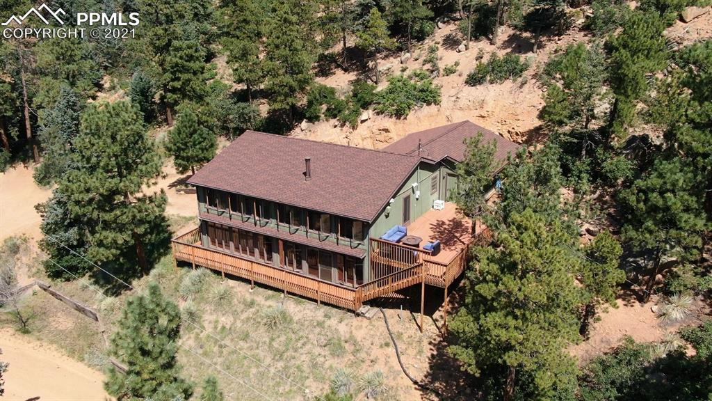 Unique, BEAUTIFUL mountain home in the exclusive gated Crystal Park community of Manitou Springs! Stunning Mountain Views! Packed with recent upgrades: high grade wood laminate flooring on the main level, new carpet in the basement, new paint throughout the home, upstairs bathroom remodel, newer range/oven, kitchen remodel and new garage door. The home is complete with a home water filtration system/water softener and passive solar heating system, wood burning stove, multi-level decks (perfect for grilling, yoga, entertaining, reading, sitting by the fire pit) and a new well pump (2021) and radon mitigation system. The two story greenhouse gives the home an open, inviting, mountain feel! A mountain escape with easy access to Manitou Springs, hiking and mountain biking trails, and several dining options!  The neighborhood boasts a really cool mountain clubhouse that is great for entertaining and also has a private neighborhood pool. A true Colorado home!