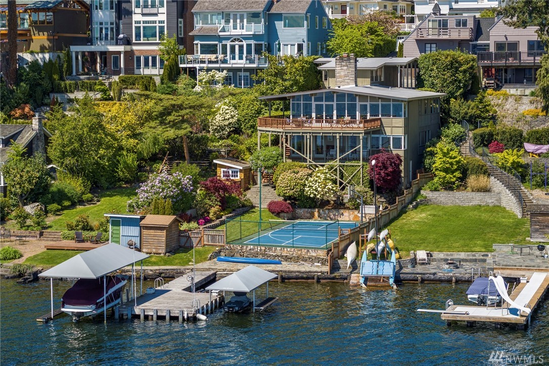 A house designed to take in close and personal views of Lake Washington, Mt Rainier & the Cascades. Mid Century dreams with walls of windows streaming in light & joy. 50ft of Waterfront, Dock w/ 2 covered boat lifts. 4 Beds, 2.5 baths. Multiple levels of decks & entertainment spaces overlooking a level yard with epic sport court set right on the waters edge that adds excitement to every swing. Views and water access like this are extraordinary to come by. Special is an understatement here.
