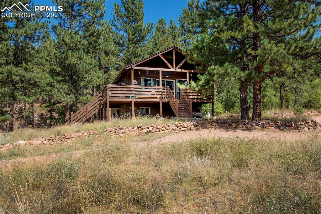 One of a kind cabin situated on 1.3 acres just 12 miles from Woodland Park. This ranch style cabin has a large front porch that offers amazing views of the mountains and the community lake. Upon entry you are greeted by warm traditional knotty pine plank walls and vaulted ceilings. The eat in kitchen includes granite counters and custom cabinetry. Enjoy plenty of natural light and expansive views from the living room that walks out to the front deck. The main level also includes a full bathroom and two bedrooms with an ample amount of space. The master walks out to a private patio that offers supreme privacy. The basement has another bedroom with plenty of closet space, a 3/4 bath, a laundry room a large bonus room that has a hot tub that walks out to the side yard. The backyard includes a gated area for canines and plenty of trees that add plenty privacy to this amazing lot. The community lake is open for fishing, boating and is in close proximity to Pike National Forest that offers plenty of hiking and trails. This cabin is truly turn key as it has a newer roof and fresh exterior paint