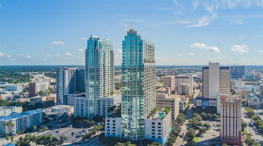 Come experience the most breathtaking views the city has to offer! This is your opportunity to be a part of the luxury premier condominium community in downtown Tampa, SkyPoint.  Located in the cultural arts district of downtown, this RARELY AVAILABLE, 25TH FLOOR, SOUTHERN EXPOSURE 2-BEDROOM, 2-BATHROOM CORNER UNIT has 10' foot floor-to-ceiling glass windows featuring stunning views of the downtown skyline, Tampa Bay, Hillsborough River, and the Garrison Channel. Watch majestic sunrises from your private balcony. The unit features gorgeous exotic Brazilian cherry hardwood flooring throughout, remote controlled sunshades in living area and blackout in master bedroom, all high-end finishes with exquisite plush frieze carpeting in the bedrooms. This fabulous floor plan boasts the largest square footage of all 2-bedroom units in the building, with an oversized laundry room with plenty of storage.  It features unlimited possibilities with a dining room and living room that is perfect for entertaining. The kitchen is complete with a granite island, subway tile backsplash, and stainless-steel appliances. This unit includes two conveniently located parking spaces on the 3rd floor of the gated access parking garage. Experience resort-style living with 24-hour concierge service, controlled building access, 8th floor amenities that include a heated pool deck, saltwater hot tub, multiple fast-starting outdoor gas grilling stations, outdoor kitchen and entertaining area, shaded pergolas, an outdoor park in the sky complete with lush landscaping as well as a resident fob access bike room and car wash on the first floor. The inside clubhouse features a catering kitchen, bar, lounging areas, flat screens, billiard table, and home theater room, all in the heart of downtown overlooking Curtis Hixon Park. Amenities also include state of the art dual fitness centers, cardio room with yoga area and separate weight room. Enjoy the walkability of an urban lifestyle with plenty of restaura
