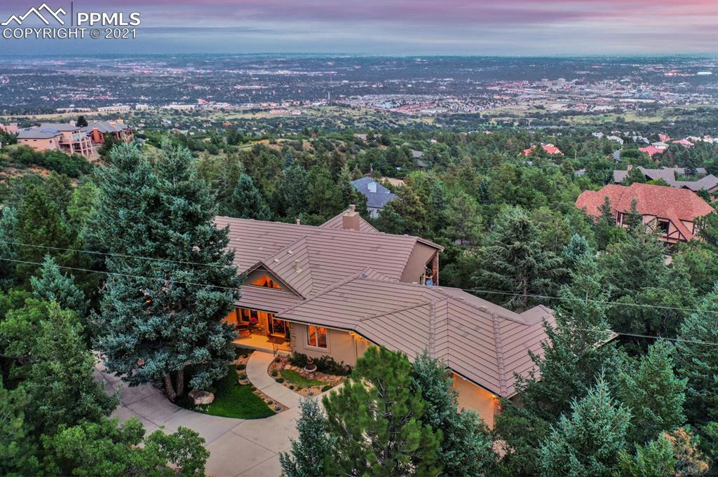 LUXURY CUSTOM MOUNTAIN HOME WITH AMAZING VIEWS OF THE CITY! This house is ideal for those that want privacy and a secluded feeling of being tuck away on top of a mountain while having easy access to trails, D12 schools, and the amenities you desire. Such care and thought have gone into designing this home along with timeless architectural details. Extensive stonework, vaulted wood plank ceilings inside and out, coved ceilings, built-in cherry cabinets, gourmet kitchen, circular staircase, Pella windows showcasing the views from every room, all above grade rooms and walls of glass capturing the natural setting. The owner's vision of creating a private sanctuary with everything you need on the main floor and incredible outdoor living spaces was completed with perfection. The main level entry welcomes you to the great room with vaulted ceilings, Pella Windows all along the wall w/electric shades, double-sided FP shared with the gourmet kitchen. This fabulous kitchen is ideal for the cook in the family with an eat-in casual dining area & walkout to the amazing covered Trex deck. Formal dining room with coved ceiling. The unique layout of the primary suite was designed to include the office and offers built-in cherry cabinets and gas fireplace and access to the deck. Relax in the en-suite 5pc bath with steam shower & jetted tub after a long day. Attached laundry room with built-ins off the master. The spiral staircase leads to the walkout lower level. The family room with FP & wet bar adjoins a space for a game table or a 2nd office. Two additional bedrooms, 2 baths, and an incredible FLEX room/bedroom. This space has a private entrance & separate driveway w/access off Loop Lane. Ideal space for a home business, in-law quarters, nanny quarters or your private gym. Keep your green thumb going all year round in your heated greenhouse Walk out to the lower covered patio & enjoy wildflowers, veggie garden, beautiful landscaping and the serene setting. Endless trails nearby.