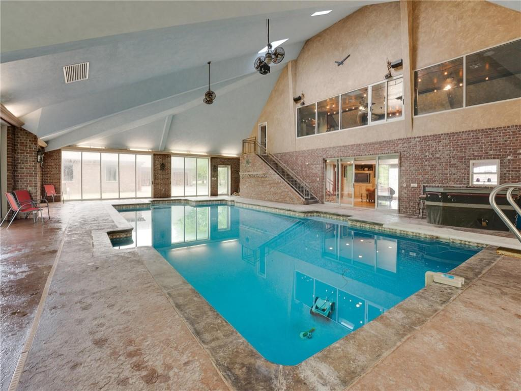 Unbelievable home in Moore, OK! This amazing home sits on 4.1 acres surrounded by trees. This custom built, one owner home has something for everyone. From the indoor pool, outdoor kitchen, guest quarters, and the 30x50 shop, you will have to see it to believe it! The main home has 4 bedrooms upstairs with the master bedroom downstairs. The pool house was built in 2007 and has a full kitchen, pantry, 1.5 baths, & bedroom. Upstairs is a huge man-cave with wet bar. The roof is Davinci slate. Welcome home!