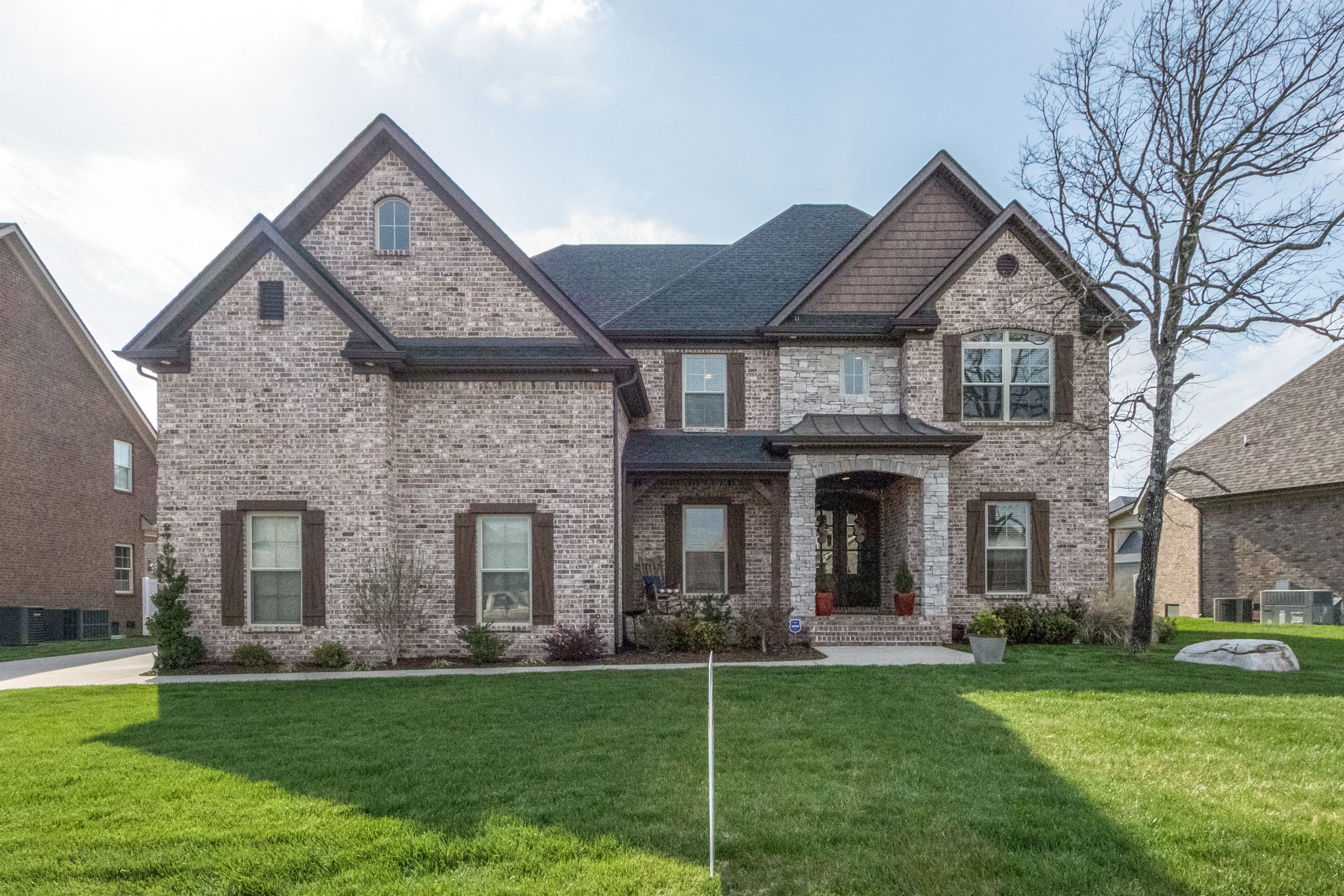 This prestigious brick & stone beauty is a must-see! 2 Bedrooms on main level, 2 up! 3 FULL Baths! 2 Bonus Rooms!! OPEN FLOOR PLAN! All HWs & Tile Downstairs, no carpet down! Spacious Laundry! Custom built-ins in all closets! Stunning Kitchen w/Pantry! Walk-in Storage! Covered/Screened Rear Porch. Full Yard Irrigation! Convenient location!