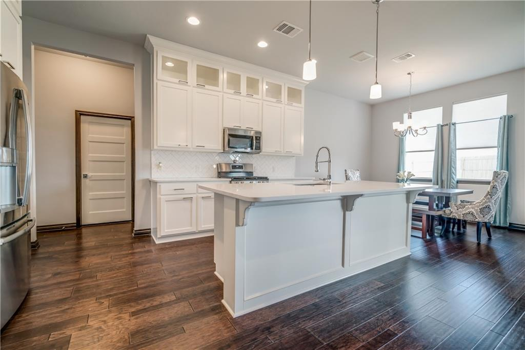 Better than new in the heart of Edmond w/LOTS of upgrades in this transitional home. From the minute you walk into this exquisitely cared for home you'll fall in love w/the attention to detail from the floors to the ceiling. This home bodes 3 nice sized bedrms & a sep study that could be used as a formal dining or add'l living/flex rm.  Beautiful hardwoods throughout the living, entry, dining, study & kitchen. Living is adorned w/floor to ceiling stone fireplace, built in floating shelving & cabinetry. Generously sized laundry w/extra storage/cabinetry. Master suite is adorned w/a custom walk in shower, double vanities, sep water closet & walk in closet w/built ins. The kitchen is a chef's dream w/upgraded kitchen cabinetry w/accent lighting, subway tile backsplash & high end quartz counter tops. Extra perks added after construction - cabinet hardware, door handles & locks. Wood blinds, new kitchen faucet, Toto toilets & a fabulous screened in porch w/full privacy fenced backyard.