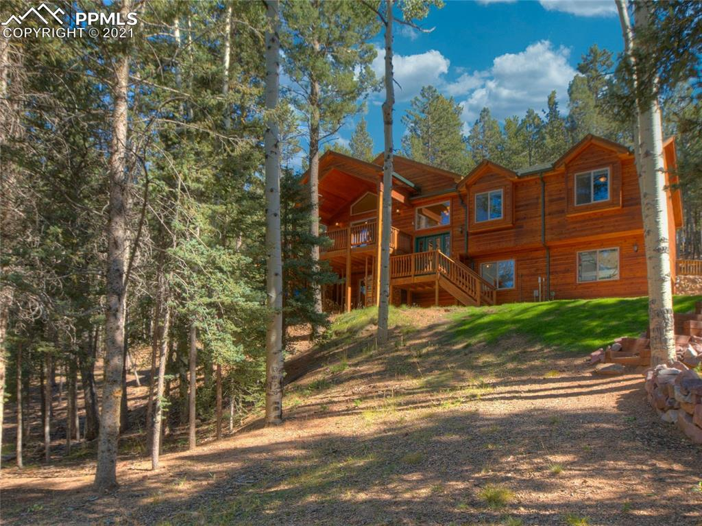 """Fantastic mountain property on over 1.5 acres, surrounded by Aspen trees is nestled in the """"City Above the Clouds"""" in Woodland Park. Less than a 15 minute drive to downtown Woodland Park, and a 10 minute walk to the famous Catamount Trail. Immediately notice the soaring vaulted ceilings and beautiful Oak hardwood floors throughout the living room, kitchen & dining room. The wood-burning fireplace in the living room walks out to very large wrap-around deck and hot tub. The kitchen includes stainless steel appliances with granite tile countertops and an island with counter seating.  Master bedroom includes a walk-in closet and a full bath with renovated shower to include river rock flooring and a bench seat along with electric radiant heated bathroom floor.  Two additional bedrooms and a full bath complete the main level. The lower level consists of a family room that walks-out to outdoor space, and office (or 4th bedroom) and a full bath. There is also a free-standing gas/propane stove along with the laundry room. The attached 2 car garage is completely finished with a new epoxy finish. There is a finished exterior building that has wood flooring and wood-planked walls with electricity, attic space, and large basement storage. The wood piles stay to keep you warm throughout the winter. Other features include new carpet in the bedrooms with upgraded padding, refinished cedar siding, and everything is in pristine condition. This mountain getaway is not one to miss!"""