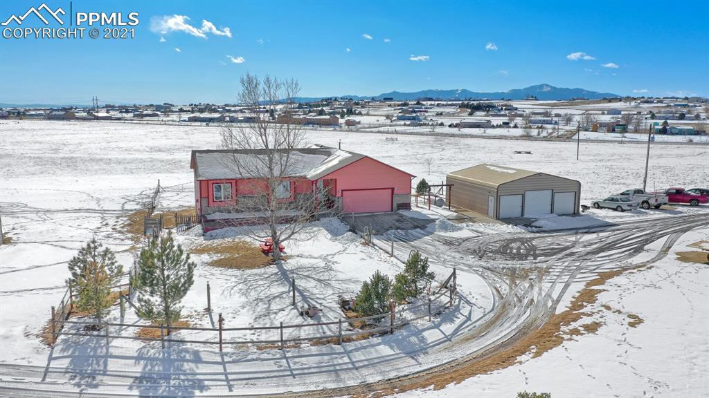 """Custom stick built ranch home on 40 acres zoned for horses & only 10 minutes from town!**Great condition*super panoramic mountain views**30'x 12' redwood deck you can access from either the great room or the master suite.  The walk out lower level (w/9 ft ceilings) is finished with 2 additional bedrooms, full bath, 2nd kitchen, 2nd Living/Family Room, and a Rec Room!  Vaulted ceilings on the main level with great room, to include a pellet stove, which heats the entire house!  Large kitchen with center island.  Main level laundry/mud room features a deep sink between the garage and the kitchen. Newer roof, newer windows, and freshly painted.  The master has a walk out to the redwood deck with mountain views.  The master bath has a huge glass block shower, complete with 2 shower heads, double sink vanity and 2 large walk in closets.   Other features are; *Custom built 3 poled ranch entryway *Colored and stamped decorative concrete front patio deck area * Solar powered electric gate with intercom and secured access control from house * Authentic buckboard wagon at entrance from mid 1800's * Other misc antique farm and ranch equipment out on pasture as decor' *Crushed Basalt driveway with concrete finished between attached and detached garages * 30'X35' 3 bay steel garage/workshop with LED lighting and 220 already installed for welding or convert to 50amp RV hookup etc * 24'X36' Barn with loafing and hay storage along with tackroom * 100'X125' corral attached to barn with power onsite, heated water troughs *20'X20"""" storage shed additional workshop with built in shelves *20*20' Metal carport for tractor or equipment storage *Property completely fenced on entire acreage *Decorative 12' & 16' maintenance free windmills * Southside of property has a dug out 125' clearing that can accompany up to 9 station outdoor gun range"""