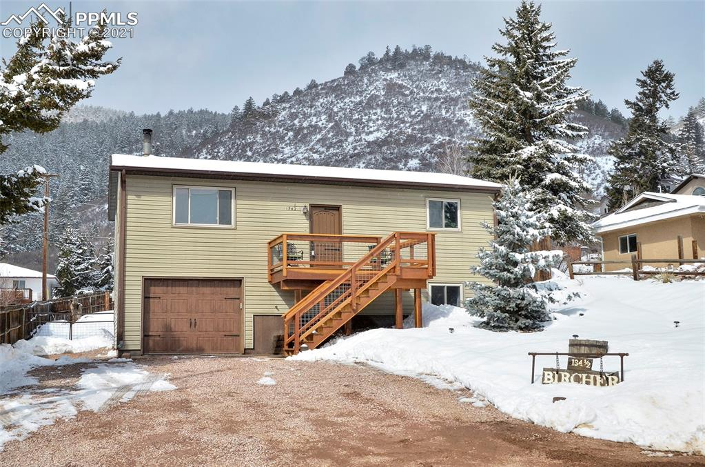 This clean and move-in ready home has been well maintained.  Need a great spot to watch the lighting of Palmer Lake's star?  Want to enjoy the sparkling city lights?  Drawn to gazing upon Spruce or Ben Lomand Mountains?  Now is your chance to do so from your very own newer deck.   As soon as you pull up you will be impressed by the attention to detail, such as nice siding, newer deck, matching garage and front doors.  Inside you will love the newer (2020) upper-level flooring and (2021) lower-level flooring.  The Lopi wood burning stove is perfect for cold winter nights.  Newer French doors lead you out to the amazing 16 x 16 deck and fenced back yard.  The kitchen has a gas range and stainless microwave and dishwasher.  Both bathrooms have been updated with newer tile, sinks, vanities, fixtures and lights.  Fall in love with the solid wood doors on the upper level.  The house is currently set up with the owner's suite on the lower level. There is an en-suite bath with walk-in closet and separate commode.  Brand new carpet as of last week.   You will find ample storage under the stairs and in the oversized 14 x 25 garage with work bench.   The layout is conducive to multi-generational living due to a larger bedroom on each level.  The furnace and water heater were replaced in 2020.  The spacious lot is xeriscaped for easy care.  Lots of room for RV parking as well.  Minutes from the cool town of Palmer Lake.