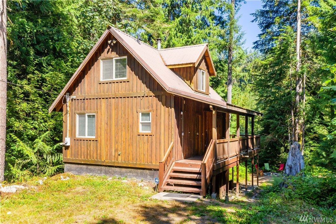 Enchanting A-Frame Skykomish chalet sited on double lot among fir trees in highly desirable Timberlane Village Community. Great year round nature retreat just 1.5 hours from the city, minutes from Steven's Pass Resort. Perfect lodge for skiing, fishing, hiking, trail walks. Amenities offer BBQ, picnic tables, river access. Cozy, rustic ambiance w/propane furnace, wood burning fireplace. Furniture and household goods remain, turn-key vacation rental potential for income opportunity. Sold as is.