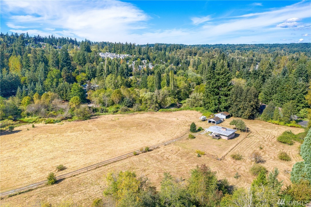 Opportunity knocks! Potential for building your dream home and/or having a horse pasture just shy of 7 acres.  Private level lot across the street from a therapeutic equestrian riding center.  Bear Creek and Mackey Creek run on the sides of the property. You can live in the charming cabin while you finalize plans for your dream home. Great location near Redmond Town Center and Microsoft.  Last sold in 1986.  Don't miss this amazing opportunity!