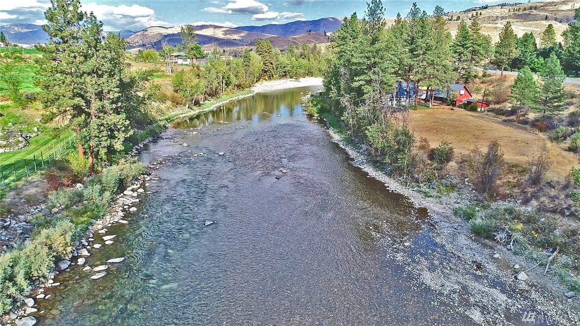 2Bd 2 Bth Home on expansive Methow River frontage. Stone fireplace, open floor plan, and 2 wood stoves. Deck right above the river, great fishing hole,  sandy beaches, meadows, treed areas all along the river. Just above riverfront that goes on and on is a level bench with park like areas, horse paddocks, and room for pasture and garden. Secluded, private, tranquil. Detached 2 car garage with finished room above. Numerous outbuildings including root type cellar with additional storage.