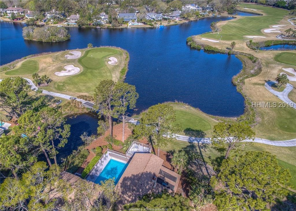 Spectacular lagoon | golf views from this one-of-a-kind home on Mooring Buoy overlooks 5 holes | 2 greens of the  Jones Golf Course & 11-mile lagoon.  Private dock, upper sitting deck, 5 BED | 6 FULL & 2 HALF BATH home. 2 private guest suites accessible from upper-level exterior,  2-car garage, 2 fully-equipped kitchens, 2 dining areas, 2 fireplaces, 2 bars, 2 steam baths, granite counters, saturnia floors, elevator, wine cellar, board games, flat screen TV's, stereo, WiFi. Exterior: large heated pool, pool deck, laundry room w bath, TV & fridge. 3 minute walk to beach. Built by former Gov. of SC.  24-hour security.  Owner SCREA (.)