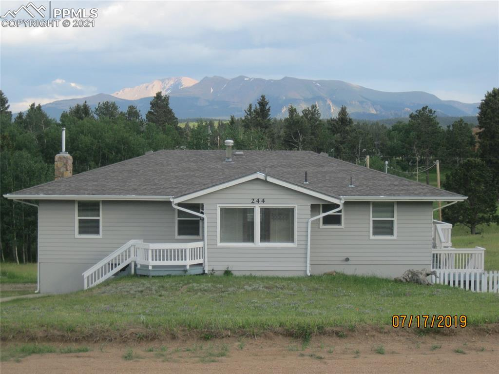 Country Home on 2 Gorgeous Acres with Pikes Peak Views- Just Outside of Woodland Park! Bring Your Horses Here - or Just Enjoy The Usable Pasture Land and Aspen Forest. Inside You'll Find Wonderful Natural Light Throughout Main and Lower Levels. Country Kitchen Boasts Parquet Floor and Plenty of Cabinetry Along w/ Extra Storage in Double Pantry. Open Living Room Has Hardwood Floors Along w/ All 3 Bedrooms on Main Level. Downstairs Has 2 More Spacious Bedrooms, Hallway Nook, and a Versatile Domestic Room by Garage Entry....