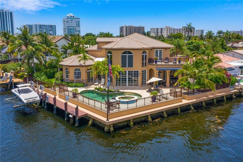 Beachside Direct Intracoastal Point Lot location. Huge travertine & beautifully landscaped patio & pool. The spectacular location provides panoramic views with 150' of waterfront.  The home offers a huge two-story great room and walls-of-glass overlooking the pool, hot tub, & Intracoastal. The oversized first-floor master suite has a 12+ ft ceilings, huge closet, onyx top wet bar, custom tiled bath. The outdoor covered living space includes a kitchen with grill, wet-bar, and 2 beverage refrigerators, seating area with TV, and full cabana bath. The kitchen is a cook's dream with Wolfe and Sub-zero appliances, gas cook-top, and plenty of storage and counter space. 25,000 lb boat-lift on the canal dock. Walk, or golf cart ride, to beaches & village restaurants. Home can be sold furnished.