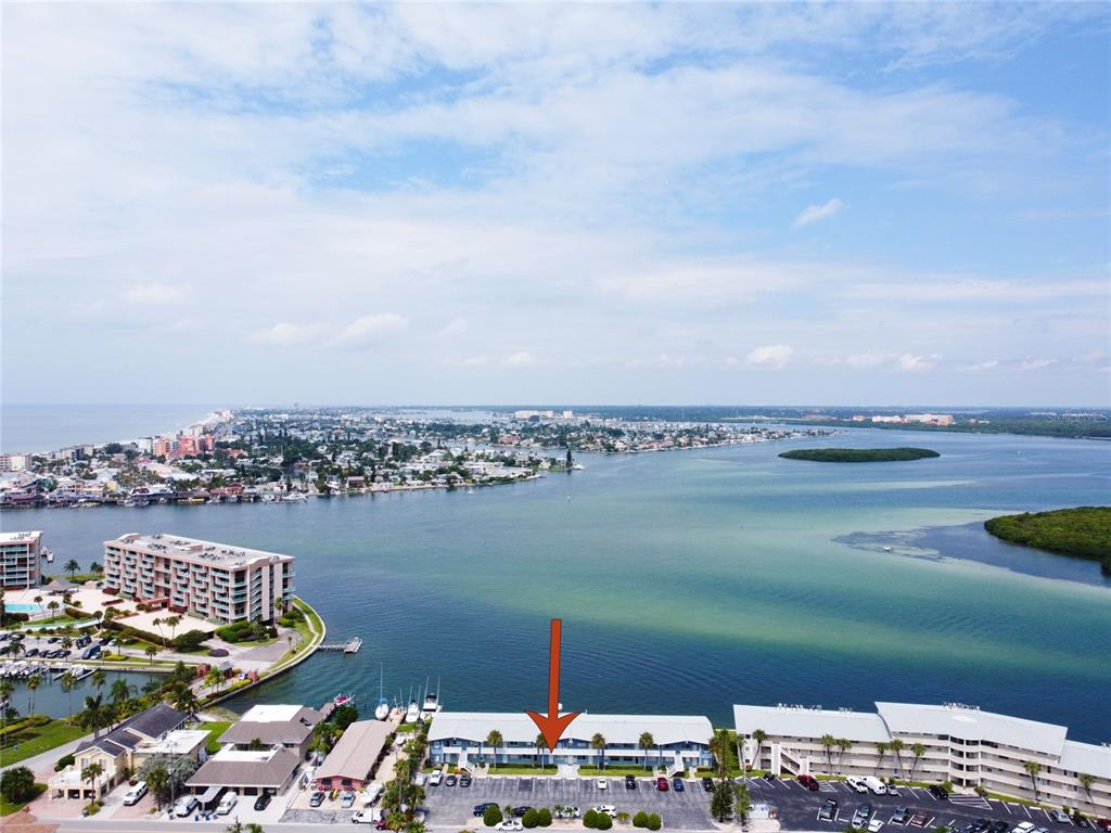 Enter this direct waterfront coastal cottage/condo. This ground-floor unit has direct access and views to Boca Ciega Bay and John's Pass. Sit on your patio and grill or on the dock and watch nature go by, Dolphins, manatees, birds, not to mention a boat parade 24/7. Almost floor to ceiling, wall to wall windows on waterfront side with lots of natural light. Inside is very spacious with lots of storage and built in wall cabinets unit is totally updated with new kitchen and engineered hardwood flooring, new high impact Windows and doors, HVAC installed in 2016, new roof and exterior updates in 2017. Capri Isle Garden is centrally located, 10 minutes to eclectic Saint Petersburg, 30 minute to Tampa and it's airports, minutes to grocery stores, restaurants, beach bars, nightlife, world famous John's Pass and of course the #1 Beach in America. Start enjoying the Florida lifestyle, bringing your fishing gear, kayak, sunscreen and your pet....25llb limit. Please be sure to check our virtual drone video of property and surrounding area.