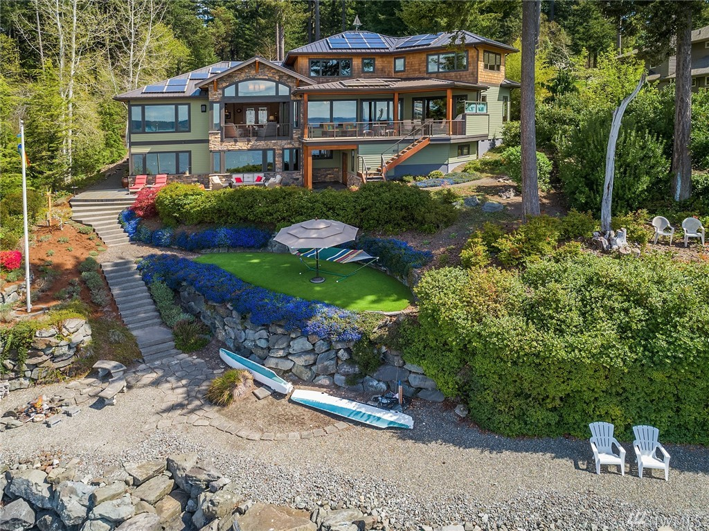 Completed in 2012, this custom NW Contemporary offers spectacular waterfront living. Natural surfaces reflect the sustainable materials used to build the house. Open floor plan with sweeping views of Henderson Bay. Nanawall doors allow for seamless indoor/outdoor living. Gourmet chef's kitchen opens to covered deck. Main floor master suite with views and hot tub access. Upstairs, two ensuite bedrooms plus rec room. Highlights include luxurious home theater and 102 feet of beachfront.