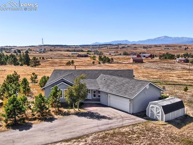 Custom Rancher on 5 acres, zoned for horses.  This 5bd/3.5bath home boasts unobstructed views of Pike's Peak and the Front Range from multiple areas in the home as well as from the two large decks and concrete patio!  Beautiful hardwood and ceramic tile throughout the house, as well as new paint and carpet make this home move-in ready.  Enjoy gatherings in the large dining room and eat-in area, while enjoying those phenomenal views.  Main level has Master Bedroom plus two other bedrooms and convenient tiled Laundry Room.