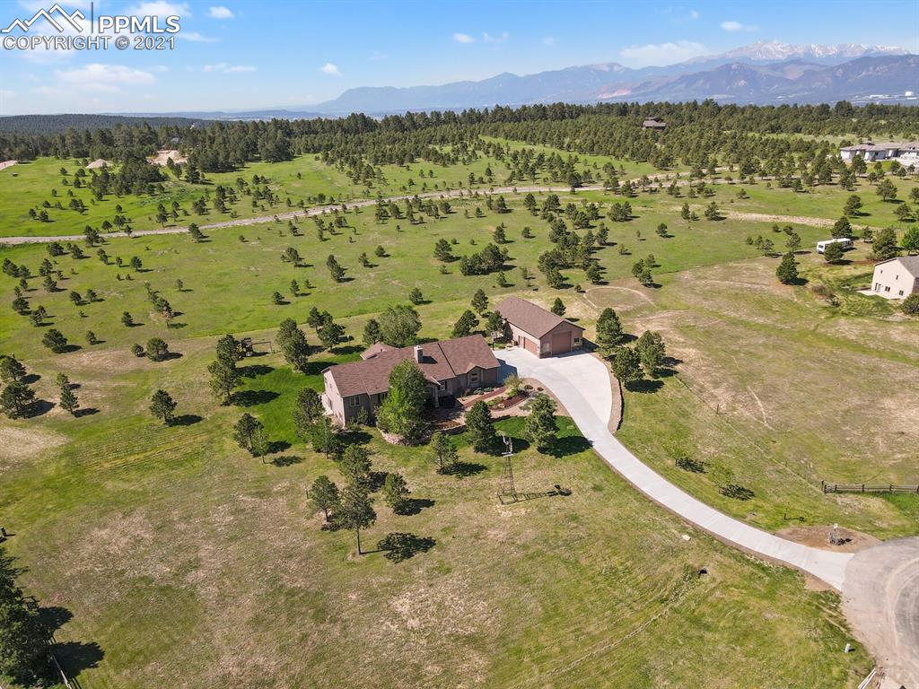 Come home to Colorado living at its finest. This stunning and spacious custom home on sits on 2.79 acres in Monument. The open floor plan offers main level living with a walk out basement. Enjoy all the top end finishes in the spacious kitchen with custom cherry soft close cabinetry,  large granite island &  5 burner gas stove top with oven and side oven. Many convenient features: formal dining room, open floor plan on both levels, central vac, porcelain tiles, covered composite deck, new cement driveway & stamped concrete.  The basement features a large family room, custom wet bar with alder cabinets, and a hidden vault room. There is so many upgrades but still a huge bonus to mention. The separate completely finished shop/oversized garage30' x 60' with large 14' x' 14' door, another 16' x 8 garage door, and even a full bathroom. This shop could be used for many purposes.