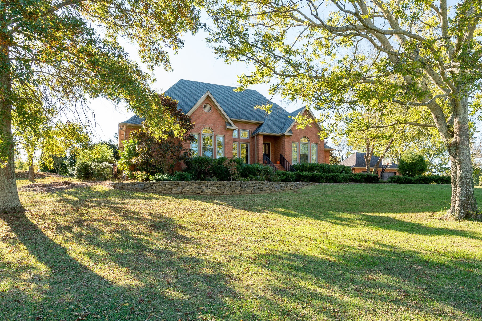 Seldom does a home under $1M come available on Old Natchez Trace. This one has it all-beautiful brick  home with upgrades, 3+ acre lot, barn & outdoor kitchen. Completely fenced so bring your animals. 4 stall barn currently used for shop & grillling/party area, kennel. Open entry to dining and living area (14' ceiling w stone fireplace) eat-in kitchen w gas cooktop; tile sunroom w windows all around. New windows & some doors. Beautiful setting on one of TN's favorite historic roads/Harpeth River