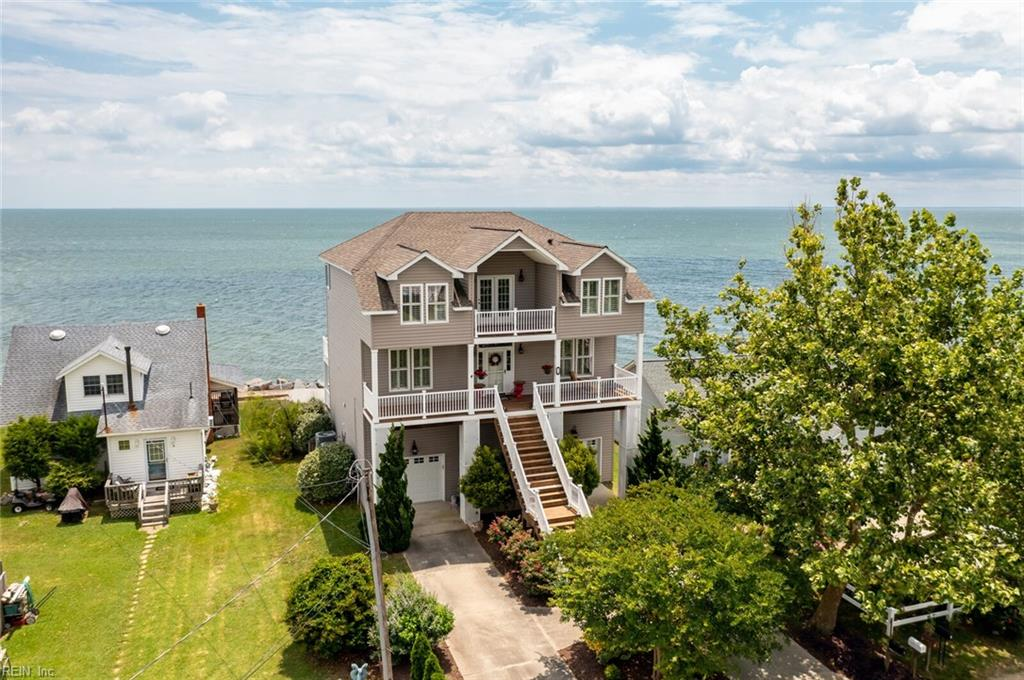Beautiful home right on the Chesapeake Bay with approx 3200 sq ft of living area plus dual garages. There are upgrades throughout including an architectural shingle roof, built-in humidifier, 2 zone HVAC, driftwood gas log fireplace, remote controlled sun shades on some windows and the 2nd level deck, hurricane shutters, generator hookup, and all 4 bedrooms have their own en-suite bathroom. The 1st floor is perfect for a gym, home office, or entertaining area w/ a wet bar w/ a mini fridge. The 2nd level has a bedroom, large great room that is open to the kitchen & 2 dining areas, and the kitchen has granite counters, stainless steel appliances, separate prep area, & a large pantry. The 3rd level has 3 more spacious bedrooms and the primary bedroom has a tray ceiling, dual walk-in closets, dual sinks, jetted tub, and separate shower. There are huge decks on all 3 levels, all with panoramic water views. The laundry room has a sink, an area to hang clothes, & a counter for folding.
