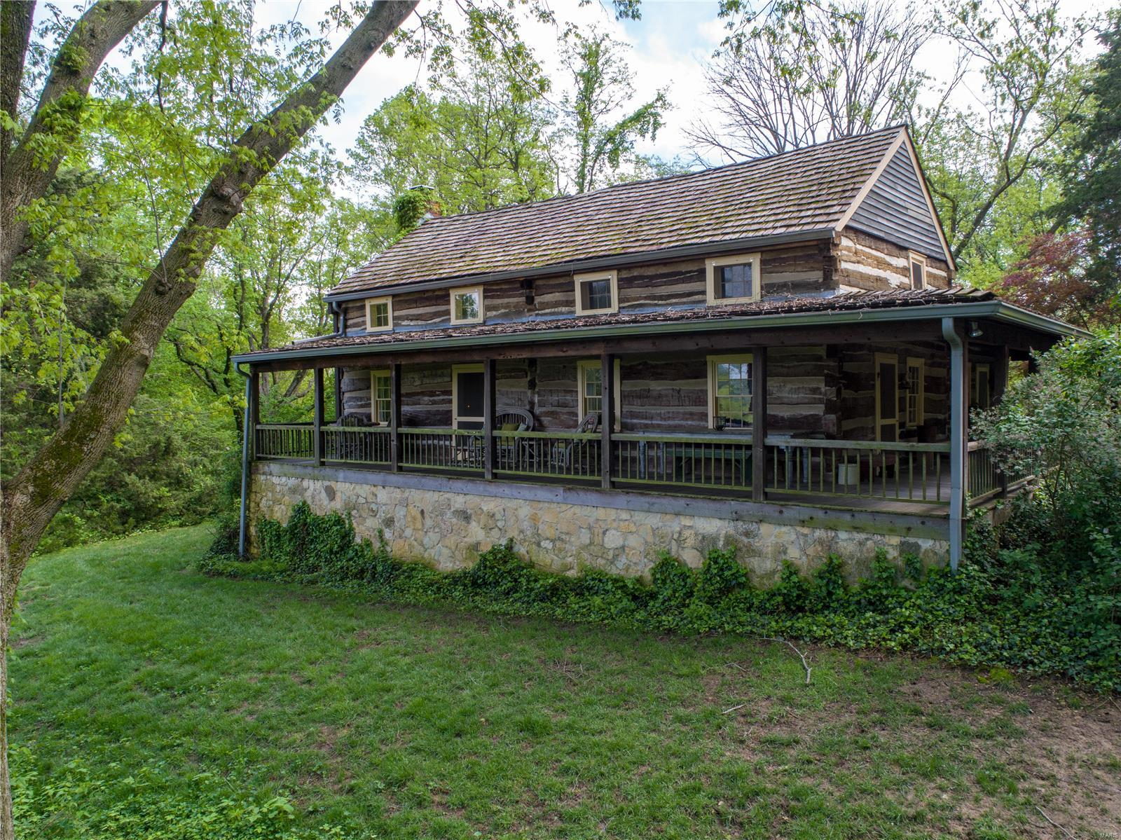 Located only 30 minutes from 270 & 44 is this enchanting compound of structures. Overlooking the Missouri River Valley is this completely private 7+ acre parcel of land with mature trees and lush woodland gardens. The main log home has been meticulously preserved and enhanced for today's needs. A covered porch stretches across two sides of the home, providing a special vantage point of the river. The main level of the home has an eat-in kitchen and is separated from the living room by a huge stone wood-burning fireplace. Off of the living room is a parlor that can also be used as a main floor master bedroom with another fireplace. The upper floor features a bedroom and fireplace. The lower level was enhanced to be a more modern living space with a recreation room, office, and full bath. Guest cottage below the two-car garage. There is a historic log cabin that you pass as you walk to the log chapel. This special structure has hosted weddings, and services and boasts a gas fireplace.
