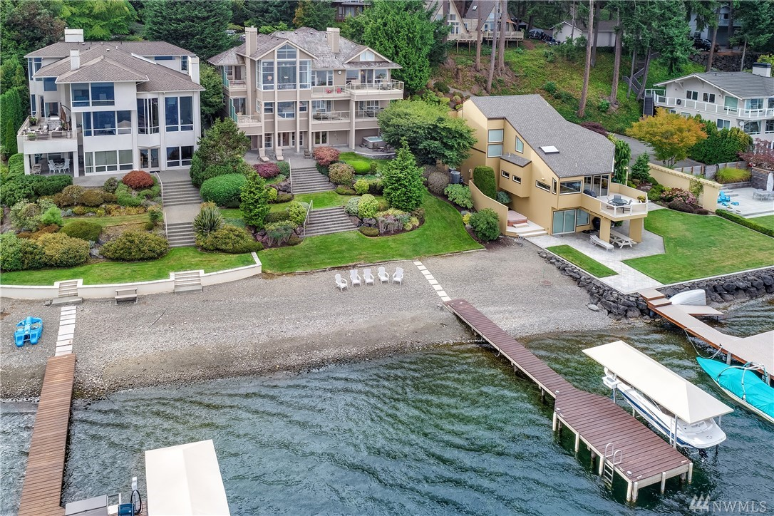 Iconic in stature w/ a relaxed lakefront disposition, this quintessential NW contemporary exudes effortless grace w/ soaring cathedral ceilings, 3 levels of luxury living space & 71' of waterfront w/ dock & boat lift framed by emerald lawns, a sandy beach & hot-tub. Dressed in sleek tile & granite, the stylish kitchen fuses function & form w/ ss appls, pantry & nearby entertainer's deck. Addtl. amenities incl. a rec room w/ wet-bar, office w/ deck, sound & security systems, plus 3-car garage.
