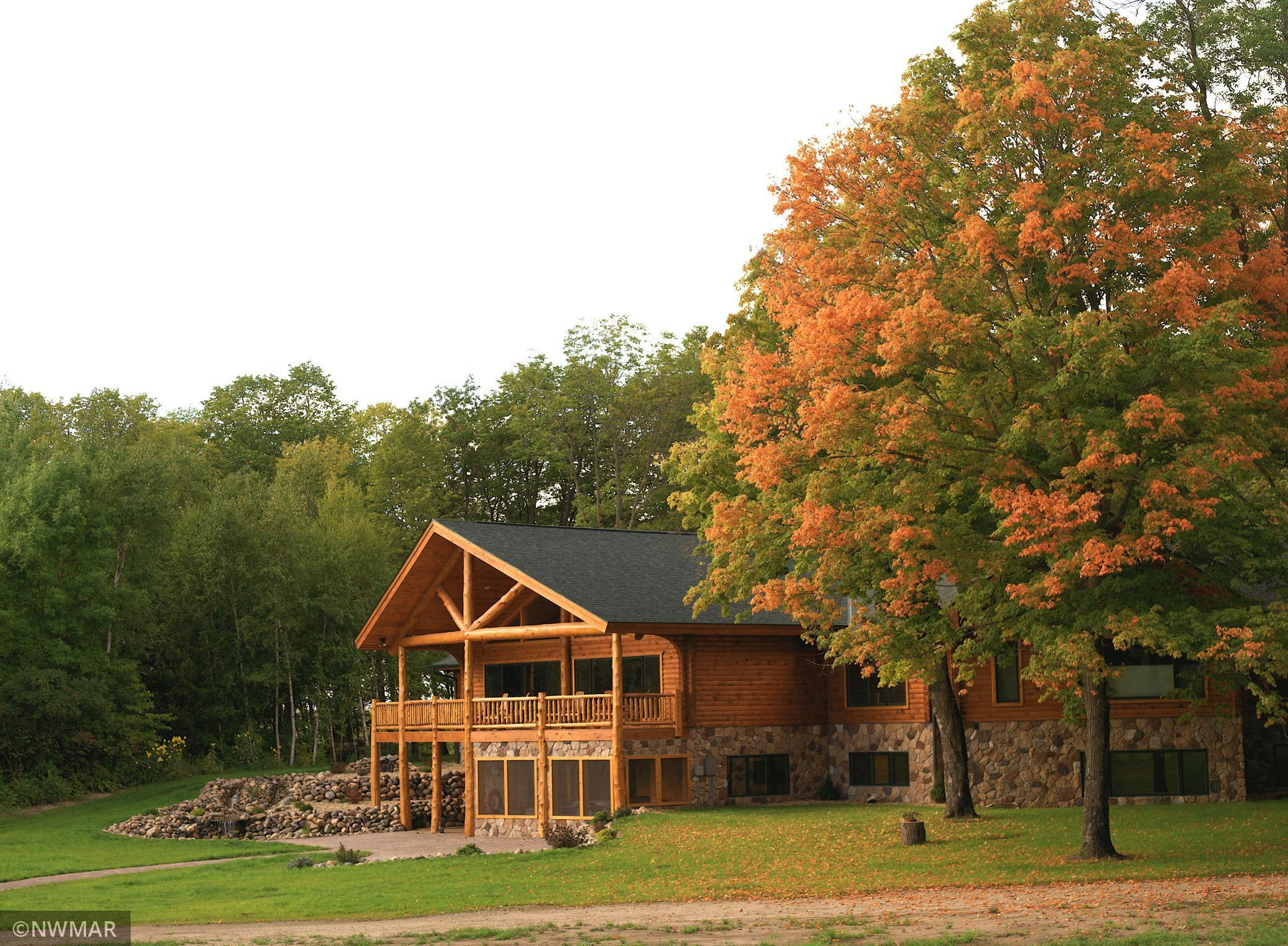 Your opportunity to own the prestigious Woodhaven Retreat on Leech Lake Sucker Bay. This stunning custom Minnesota Log Home is perfectly nestled on a private peninsula with just under 44 acres and over a half mile of lakeshore with a 100' of sand beach, a private road, and surrounded by 1000's of acres of public land. This 5 bedroom, 6.5 bath, 8,495 sq ft home features custom hand scribed rustic log railings, high-end chef's kitchen, custom hickory cabinets and granite countertops throughout, hickory hardwood floors and custom windows with perfect views of the lake and sunsets. Come relax by the beautiful stone fireplaces nestled up with a hot cup of coco and melt away in the hot  tub while you watch the bright stars on a clear evening or end your day in the sauna. Elevator & laundry on both levels makes this perfect for all ages.  Perfect for year round activities including boating, hiking, snowmobiling, and more! Includes detached garage with extra sleeping quarters, cabin & gazebo.