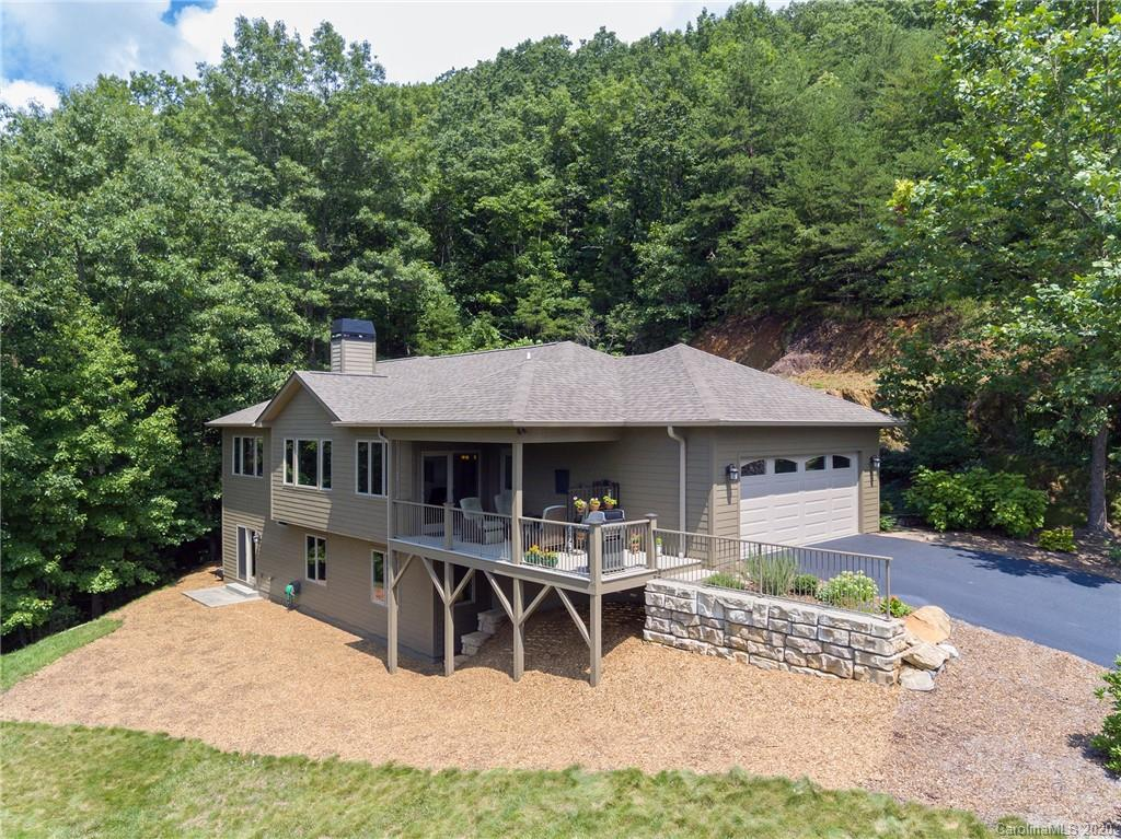 Rare offering in Black Mountain for an immaculate/like-new single-family home with long-range panoramic mountain views, a flat driveway, 2-car main level garage, and minimal maintenance! Just a 5-minute drive to downtown Black Mtn., this home features the master on the main level with walk-in closet/dual vanities/tile shower/whirlpool tub, open floorplan, wood-burning fireplace with built-ins and stone surround, vaulted living room ceiling, granite counters, high-end kitchen appliances with exhaust hood, wood floors on both levels, and beautiful landscaping. Multi-functional laundry/office on main level. Walk-out lower level features a second living room, office with built-ins and 2 additional bedrooms (one is a 2nd master suite with walk-in closet). Great vacation rental potential. Sellers purchased additional land to protect the view. This property lies just 50 yards from the Black Mtn town limits, so there are only county taxes. Pre-wired for hot tub, exterior repainted in 2020.