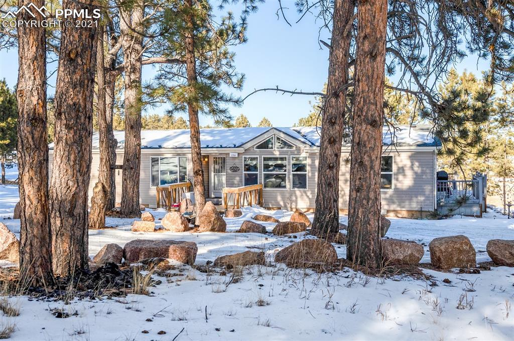 FINALLY, THIS IS WHAT YOU'VE BEEN LOOKING FOR: PRIVATE, IMMACULATE HOME IN THE WOODS ON 2.28 CHARMING ACRES—LOCATED CLOSE ENOUGH TO TELLER COUNTY 1 TO BE CONVENIENT, BUT CUDDLED BACK IN THE PINES FAR ENOUGH SO THAT YOU DON'T REALLY EXPERIENCE CR-1's TRAFFIC.  GREAT LOCATION JUST SOUTH OF FLORISSANT FOSSIL BEDS! THIS LOT IS MODERATELY TREED, WHICH MAKES IT BRIGHT BUT PRIVATE. HORSES ALLOWED.  BUILT IN 2007, THIS HOME BOASTS HIGH QUALITY 2X6 CONSTRUCTION, NOTHING LIKE OTHER MANUFACTURED HOMES. ALMOST ALL LENDERS CONSIDER THIS TYPE (UBC/IBC/IRC) TO BE JUST AS GOOD OR BETTER THAN STICK-BUILT HOMES.  FEELS SOLID—AND IT IS! DO YOU HATE STAIRS? EVERYTHING HERE IS ON ONE LEVEL. CLIMB JUST ONE STEP FROM THE DRIVEWAY ONTO ITS NEW WOODEN FRONT DECK. ENTER THE NEW STORM DOOR AND YOU FIND A VERY OPEN FLOORPLAN WITH LOTS OF ARCHITECTURAL DETAIL. THERE ARE PLEASANT VIEWS FROM ALL WINDOWS AND A COZY WOOD-BURNING STOVE IN LIVING ROOM. TO THE LEFT ARE THE SMALLER BEDROOMS, ONE BEING USED AS AN OFFICE. TO THE RIGHT IS YOUR LARGE MASTER SUITE WITH A 5-PIECE MASTER BATH, DELTA FAUCETS, BIG WALK-IN CLOSET & PRIVATE WALKOUT TO THE  48-SQUARE-FOOT TREX DECK (LOW-OR-NO MAINTENANCE). A SMALL STAIRCASE JOINS THIS MAIN DECK TO THE WOODEN DECK THAT RUNS THE LENGTH OF THE HOME IN BACK. THE LARGE AND BRITE LAUNDRY ROOM IS LOCATED BETWEEN MASTER AND KITCHEN. YOUR KITCHEN FEELS OPEN TO THE LIVING ROOM AND HAS A BIG ISLAND AND WALK-OUT. ALL KITCHEN APPLIANCES INCLUDED. LOVELY SOLID-SURFACE COUNTERS REMIND ME OF GRANITE, BUT ARE MORE SANITARY BECAUSE THEY HAVE NONE OF GRANITE'S NATURAL FISSURES. OUTSIDE, YOU HAVE A LARGE  GAS FIREPIT AMID THE BOULDERS, GREAT FOR ENTERTAINING. NEW ROOF WITH TRANSFERABLE WARRANTY. NEW DETACHED OVERSIZED GARAGE, PLUS STORAGE SHED & SHELTER FOR FIREWOOD. ONLY SIX MILES (9 MINUTES) FROM FLORISSANT, 3.9 MILES FROM FLORISSANT FOSSIL BEDS NATIONAL MONUMENT.  WOODLAND PARK IS ONLY  17.2 MILES OR 26 MINUTES AWAY. COLORADO SPRINGS IS ONLY 36.2 MILES OR 52 MINUTES AWAY.