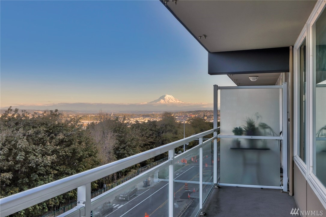 Open 2 bed/1.5 bath Tacoma condo w/gorgeous views of Commencement Bay, Mt. Rainier & city! This 900+ sf home features newer paint, laminate flooring, great kitchen w/ss appliances & a large master w/walk-in closet & ensuite half bath. Take in the stunning views any time of day or night on your balcony or from the rooftop deck complete w/pool & BBQ patio. 1 parking space in the secure garage, too! Conveniently located near the Downtown/Stadium Districts & soon-to-be new link light rail station!