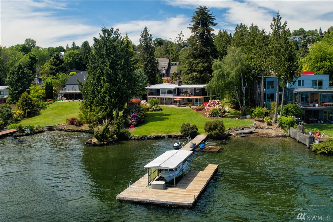 Rare find: 100ft prime lo-bank waterfront with dock & covered boat slip in desirable neighbrhd. Full Acre+ of privacy w/ stunning views fr every outlook: Lk WA, Mt. Rainier, sweeping lawns, lush native trees & gardens. Glamorous Midcentury Modern designed by Seattle's prized UW/AIA award-winning architects Lawrence-Hazen w/ pristine period details revered by purists beautifully maintained. Born for entertaining, sophisticated flr plan will transport you to 21st Century and beyond if refurbished.
