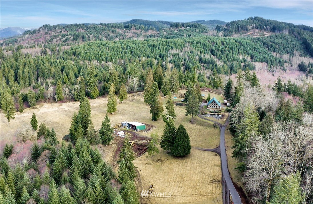 Wow, your own slice of paradise on 20 acres! 1st time on the market ~ peace, privacy & lake view! This charming & rustic A-frame offers a large upper loft w/ensuite bath & private balcony to serve as your master bedroom. Main level boasts another bdrm, bath, utility, kitchen, living & dining w/soaring ceilings & pine interior. Outside you'll find a detached 24x36 2 car garage w/16x26 workshop offering 220, woodstove + office space. Garage & shop are insulated & sheetrocked. 30x40 carport; 9x13 cottage; storage shed; woodshed; AND your own private pond w/dock, bridge & shed to store your fishing gear, etc. Zoned R10 so potential to subdivide (buyer to verify to own satisfaction). 2 bdrm home on 3 bdrm septic leaves additional possibilities!