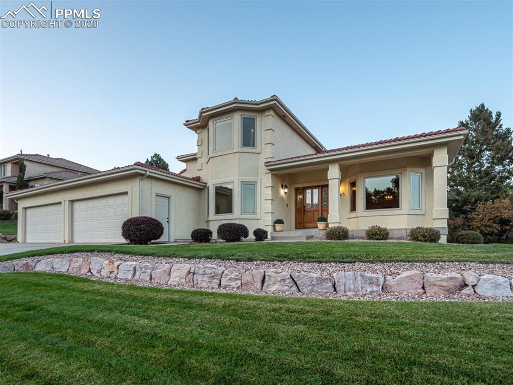 Welcome home to your beautiful custom home nestled high above Colorado Springs in Mountain Shadows overlooking spectacular city and mountain views. This home includes highly sought-after amenities on the main level such as master suite with fireplace, 5-piece bath and a large walk-in closet,  kitchen complete with new Jen-Air appliances and gas stove, Corian countertops, large island, formal dining, office with French doors and stunning hardwood floors present throughout the main. The family room has a lovely built in mantel, cozy gas burning fireplace and provides a walk out onto a beautiful wrap around covered and uncovered composite deck. The main level also has a ½ bath in the hallway, a very spacious laundry room and oversized 4 car garage. The upper level has 3 bedrooms with large closet space, 2 bathrooms and plush carpet. The lower level includes a bar, entertainment area, recreation room, bedroom, bathroom, plus two storage rooms, and walkout. Everyone has their own room to escape to. Fully landscaped with sprinklers in the natural vegetation.  Enjoy your morning coffee while overlooking a serene sunrise and views of the Colorado eastern plains as far as the eye can see. If you love fresh air and exercise Mountain Shadows offers many activities for those who enjoy the great outdoors. Open space amenities are right outside your door offering hiking, biking, trails, and wildlife at elevations up to 7000 feet.