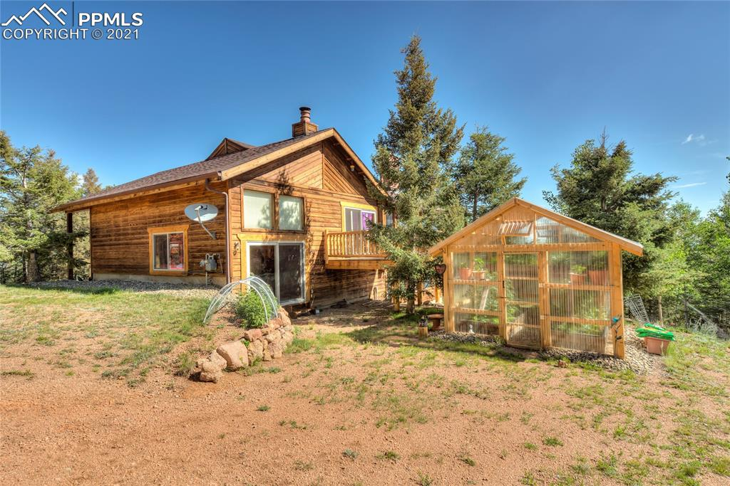 Don't miss this very private and secluded home just outside of Divide. Over 10 acres of land zoned for agricultural use. Spacious home w/ vaulted T&G ceiling, a inviting living room with wood stove, kitchen w/eat-in dining that walks-out to patio w/ a gorgeous view of Pikes Peak, formal dining room, large lower level family room w/ wood stove and a dry bar for entertaining and access to sunroom.  Among the three bedrooms, the master comes with amenities like a fireplace and a second story walk out balcony to the sunroom.