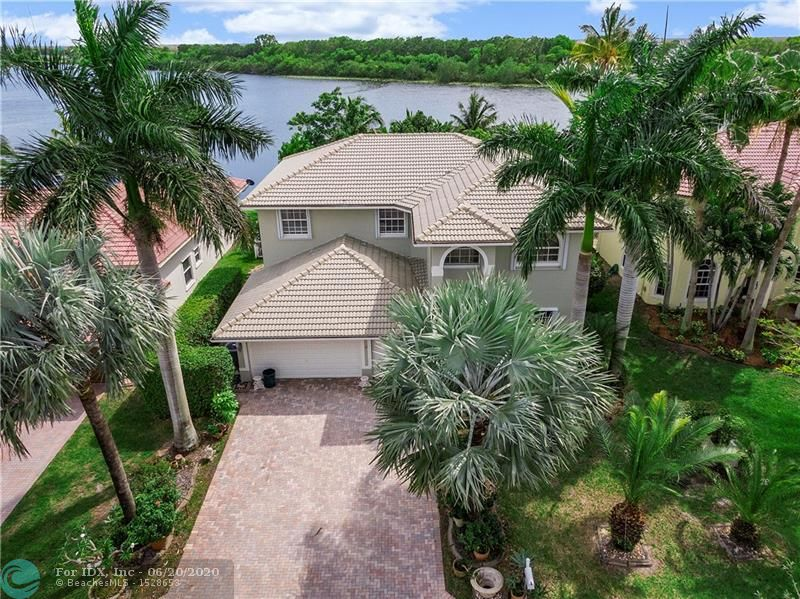 Lakefront home with wide water view in gated Pelican Isle of Coral Springs. 2nd floor has  Huge 28x19 game room with real hardwood floors as well as in all 3-upstairs BR's with in-law suite. Master BR & bath on 1st floor, double vanity,roman tub and shower. 16x16 ceramic tile floors downstairs with 42-inch Oak kitchen cabinets and granite counter-tops with an island overlooking the family room. Updated SS appliances including front load W/D. Accordion shutters on all openings & levels. Newer Dual A/C units, Lots of fruit trees in backyard (mango, jack, etc. Spacious covered/screened patio fenced-in back yard with gorgeous lake view. Low HOA only $135/mo covers lawncare, landscaping, sprinklers,and irrigation.  Close to top-rated schools, shopping and easy access to Sawgrass Xpressway.