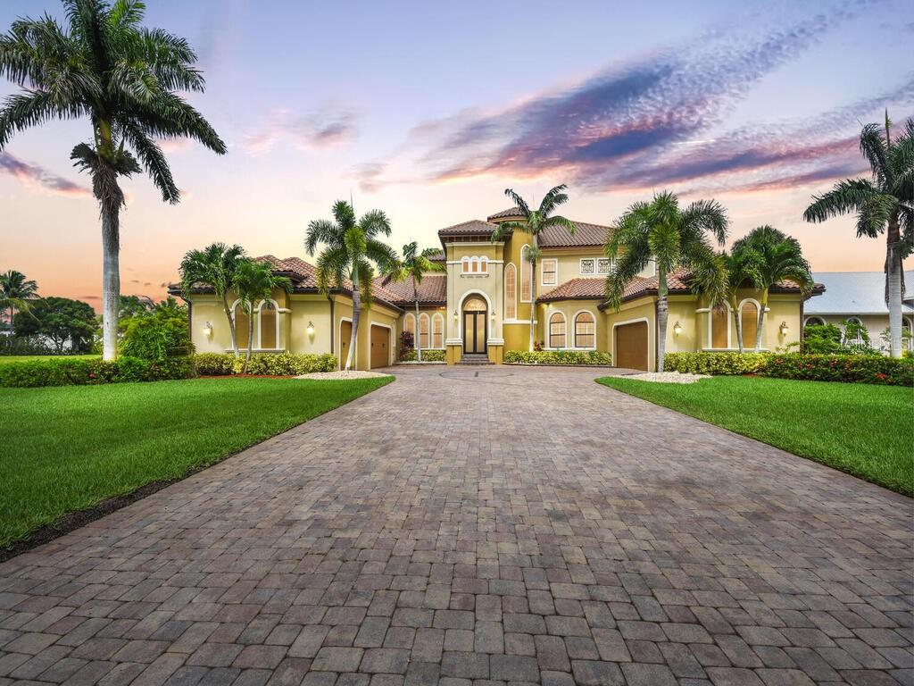 """This exquisite custom built home is an entertainers dream! Boasting over 7,000 sqft, five car garage and six bedrooms, guests are captivated by exquisite wood inlay ceilings, coffered and tray ceilings throughout. The massive living areas open to create stunning indoor/outdoor living space. The putting green lies just behind the resort style pool and caved hot tub with waterfall. Enjoy the Sonos surround sound as you grill in the outdoor kitchen, lounge by the outdoor fireplace, hit a few golf balls or practice in the batting cage. Tired of lounging and ready for a workout... head up to the home gym. The """"Man Cave"""" is equipped for a home theatre, has a full bar with custom lighting, a deck to catch the magnificent Southwest FL sunsets, and all the games needed for family fun! The home hosts laundry facilities both upstairs and down, a home office, locker or mud room, full size pantry, butler's pantry with full size wine fridge and more. This home has a deeded dock space with lift that offers quick access to the river and Gulf of Mexico. Only minutes from downtown by boat or car! This hidden gem of neighborhood hosts two tennis courts, pickle ball, and a private boat launch."""
