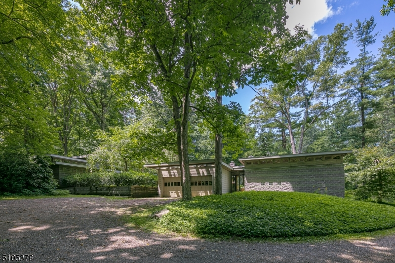 This striking custom-built modern cabin is perched hillside on historic Bernardsville Mountain. Situated on approximately 5.68 acres the property is bordered by perennial gardens, wildflowers, a meandering stream and handsome steel pool. Styled mainly with glass, concrete and other authentic materials, clear sight-lines gracefully weave indoor and outdoor spaces together. A stylish and cozy interior features a gourmet stainless steel kitchen with high ceilings, breakfast nook with fireplace, built-ins and a dramatic wall of windows overlooking the rear patio. Formal dining and living rooms, the latter with fireplace lead to two bedrooms including the outstanding master suite which maintains a sitting room and sunken bedroom with courtyard access, double-sided fireplace, expansive walk-in closet, exercise room and bath. A separate office and guest suite provide both utility and versatility to the living quarters. Other features and amenities include multi-zone radiant heat, a natural gas generator, well and septic.