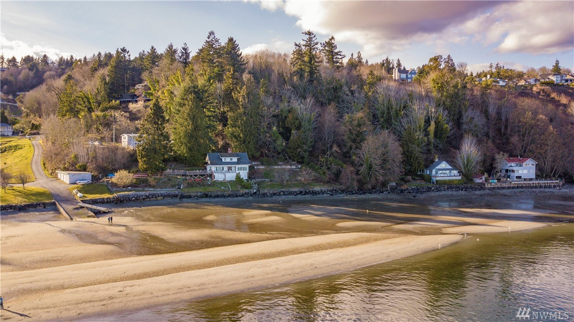 Value in the land. Unique opportunity to own 3 Tax Parcels in Gig Harbor w/spectacular views of Vashon Island, Ruston, Mt. Rainier, and Tacoma Narrows Bridge. 4 bedroom/2 bath home  on 6.03 acres located just north of Sunrise Reach. 308 ft of private beach waterfront with tide rights. Updated Kitchen w/ granite and SS appliances. Central A/C. Amazing deck. Unique investment opportunity