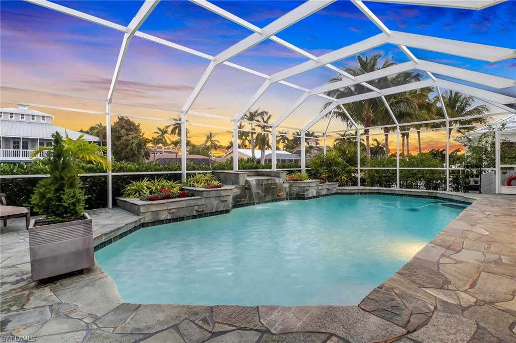Coastal Contemporary Key-West home in the boating community of Royal Harbor! Talk about WOW factor upon entering the front doors to soaring 18 ft volume ceilings finished w/ cypress wood followed w/ a direct view of your in-ground heated pool w/ waterfall & canal. Open floor plan & vaulted ceilings allow for plenty of natural light from your west exposure. Home has recently undergone countless improvements including: New air handler, heater, air conditioner, finished garage w/ its own AC, aluminum electric roll-down storm shutters, new kitchen appliances, LG washer/dryer, Rhino water filter, Kevlar hurricane screens, freshly painted roof/home exterior/pool cage/ & repainted driveway. Owner also replaced all duct work, new filtration system, pool cage, irrigation system, impact doors/windows, & gutters, etc. (See attached full list of improvements) Home is elevated meeting the FEMA min. standards for base flood elevation. Boaters! Brand New Dock & Boat Lift allowing quick no bridge access to Naples Bay & Gulf of Mexico. This is a HUGE opportunity to reside in one of the most desirable boating communities in Naples. Don't let this one slip away.