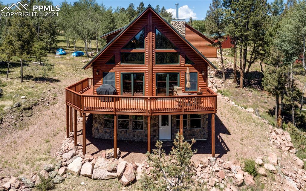 2744 sf, 3 bed, 3 bath, 5 car, 4+ acre Colorado dream property. Cedar logs from Maine, metal roof. Secluded but easy access. Fantastic Pikes Peak view from great room and deck. Main level living. Great room with rock wood burning fireplace with 2 blowers. Custom kitchen with hickory cabinets. Wood ceilings and floors. In floor radiant heat with 4 zones. RV dump and power. Three door insulated and heated detached Garage with workshop. Separate barn can accommodate 4 small vehicles or 2 large trucks.