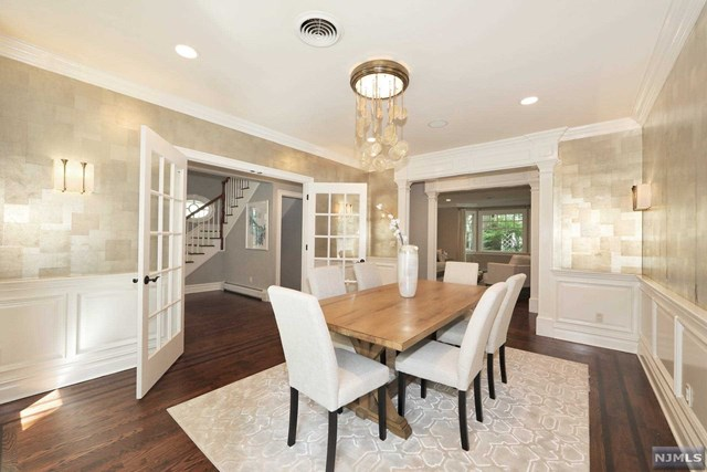 Situated on a picturesque street on Tenafly's prestigious East Hill, this like new 2007 custom Colonial, built by Jeff Gus, features signature wood craftsmanship and a superb living flow.  Stylishly decorated, this home was featured in NY Homes magazine.  A two-story entry foyer leads through French glass doors in a chic dining room.  The gourmet kitchen boasts a 6-burner Viking double oven, Miele dishwasher, Sub Zero refrigerator and wine cooler, quartz counter tops and spacious breakfast area surrounded by expansive windows.  The kitchen flows into a large family room with fireplace and continues into the formal living space.  All five oversized bedrooms with en suite baths include generous closets and tremendous windows.  The master bedroom suite features a fireplace, his/her walk-in-closet and a well-appointed master bath.  The lower level includes a California closet office and a large family / entertainment room. Walking distance to school, NYC bus and houses of worship