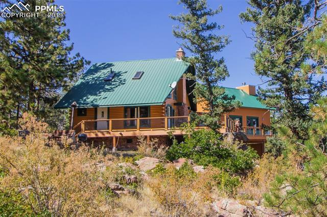 Unique custom log cabin on 20 acres with astounding views of Pikes Peak Range! Few neighbors, abundant wildlife, rock outcroppings, and beautiful vistas in all directions.  The Main level is rustic full log construction with knotty pine floors, exposed beam ceiling, woodstove, and great views from the windows.  Upper level has 2nd Family room, ¾ Bath, 2 bedrooms, skylights, and 2 nooks great for playrooms or extra storage. The Formal Living Room is simply stunning with its cathedral ceiling and impressive rock fireplace.