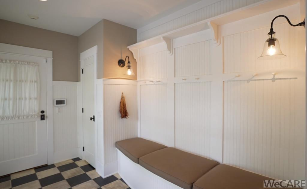 Mudroom with sconce lighting and wainscoting