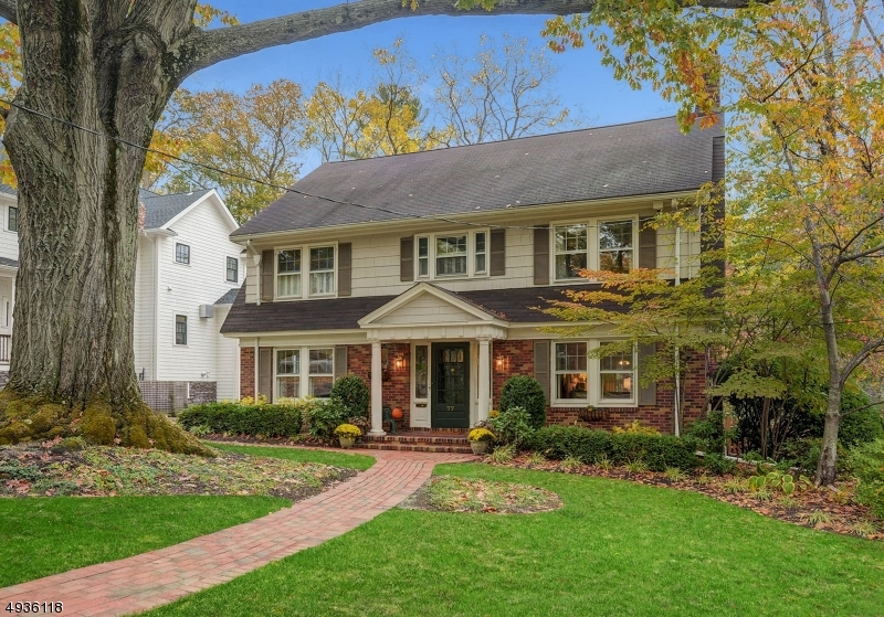 """Exquisite 6 Bedroom, 3.2 bath center hall Colonial located on a prime tree-lined street just out of town, ever so close to the vibrant village and Mid-Town Direct train. Move-in ready is an understatement. The tone is set from the moment you enter the gracious large front to back foyer, grand living room w/FP, beautiful formal dining room, first floor office, striking updated kitchen which opens to the sunken family room featuring incredible windows overlooking the large private yard & brick patio. The second floor has 4 bedrooms & 2 full bathrooms, plus 2 more bedrooms & another full bath on the third floor, one is quite large. The lower level features a finished rec room, art room and utility area.  Fireplace in """"as is"""" condition."""