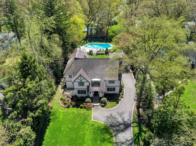 One of a kind custom built Tudor style home on .62 acre in Wychwood section. Warm and elegant, filled with sunlight. gorgeous wood floors, beautiful terrace area accessed from Kit/fam rm/DR and LR Terrace & balcony w views of stone wall & terrace-  perfect setting for in ground pool.Privately landscaped to ensure hours of warm weather fun. Butler pantry designed for entertaining & tucked away office is a bonus. Gourmet kitchen w/double dw/oven/refrig drawers/warming drawer opens to fam rm filled w/ custom built ins & gas fpl ideal for chilly evenings. Master suite w access to balcony - double walk in closets, sumptuous  bath w heated flooring & double vanities. Additionally 3 bedrooms & 2 full baths plus generous laundry room. #3rd floor suite-ideal for out of town guests provides full bath & sunfilled br
